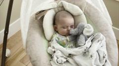 A newborn boy sleeping in swing with stuffed animal - stock footage