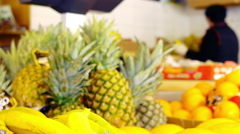 Fresh ananas fruits in the market with woman working in the background Stock Footage