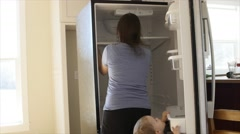 A toddler helping mother clean out the kitchen fridge Arkistovideo