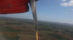 Red aircraft flies above plantations and tropical jungle Stock Footage