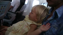 Child sits and misbehaves on father's knees in airplane Stock Footage
