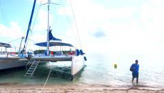 4K Man walks from Catamaran Boats on White Sand Beach on Island Paradise Stock Footage