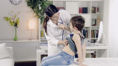 doctor visiting child with stethoscope in medical office - stock footage