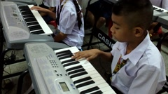 Thai Children study piano in classroom Stock Footage