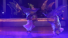 Two girls in theatrical costumes with wings dances and turns round Stock Footage