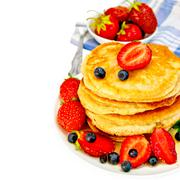 Flapjacks with strawberries and blueberries in bowl with napkin - stock photo