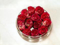 Red rosebuds in glass vase Stock Photos