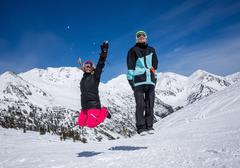 Happy couple jumping on the background of snowy mountains Stock Photos