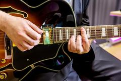 Hands guitarist playing chords in jazz band closeup Stock Photos