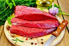 Meat beef on board with herbs and spices - stock photo