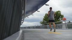 Slow motion jogger on modern bridge Stock Footage