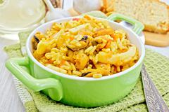 Pilaf with seafood in green pot on board - stock photo