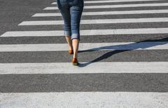 woman going on the crosswalk - stock photo