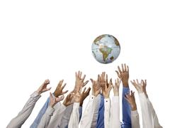 Group of hands reaching the world globe Stock Photos