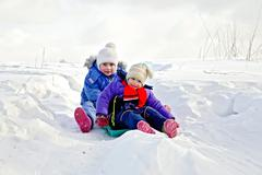 Two girls on sled in winter Stock Photos