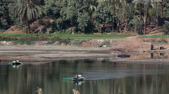 MEN WITH ROWING BOATS & DONKEY, RIVER NILE, LUXOR, EGYPT Stock Footage