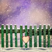 Snow-covered wooden fence with  paper heart Stock Illustration