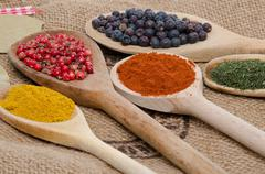 Composition of wooden spoons with juniper berries, paprika, pink peppercorn,  Stock Photos