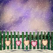 Snow-covered wooden fence with hanging on it with paper hearts Stock Illustration