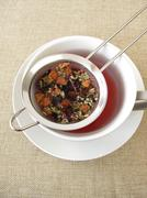 Herbal tea with fruits and flowers in tea strainer Kuvituskuvat