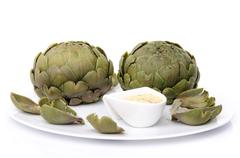 Cooked artichoke with a vinaigrette sauce on a plate - stock photo