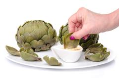 Woman's hand dipping an artichoke leaf into a vinaigrette Stock Photos