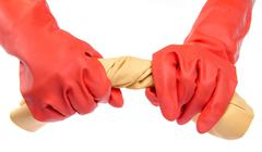 Hands in red rubber gloves wringing a cloth - stock photo