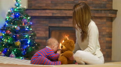 The young girl (mother) with baby at home by the fireplace Stock Footage