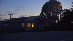 A 1940's style house with the lights on at night. Stock Footage
