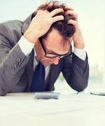 Businessman with papres, laptop and calculator Stock Photos