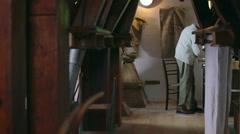 Elderly man working in the vintage watermill Stock Footage