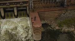 Aerial tilt shot soldier military personnel on dam lift down to pull back Stock Footage
