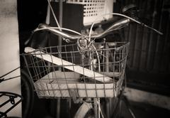 Old basket on antique bicycle Stock Photos