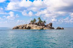 uninhabited Seychelles island - view from the sea - stock photo