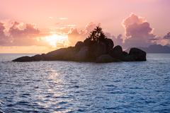 Uninhabited Seychelles island - view from the sea during sunset - stock photo