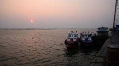 Sunset sky at sea with shillouette boat at jetty in winter season Stock Footage