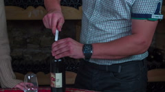 Stock Video Footage of Waiter inserts the bottle opener in to the cork