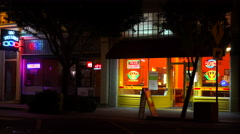 Establishing shot of a small retail storefront business district at night. Arkistovideo