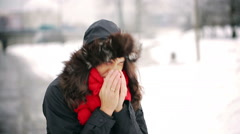 Sick woman blowing nose in the park at winter time Stock Footage