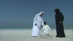 An Arabic boy destroys a sandcastle, while his parents watch him. Stock Footage