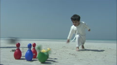 An Arab girl plays with skittles on the beach. - stock footage