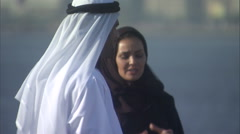 An Arabic couple talk by a lake. - stock footage