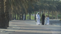 An Arabic family walks along a pathway at a park. - stock footage