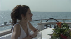 A woman has a conversation with her companion while sitting on a boat. - stock footage