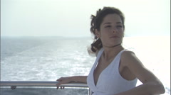 A woman relaxes on a cruise boat, overlooking the sea. Stock Footage