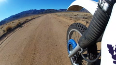Front Wheel View Of Motorcycle On Dirt Road To Mountains Stock Footage