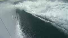 Shot at the side of a speed boat as water rushes beneath it. - stock footage