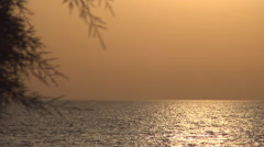Dusk landscape with sun reflection in sea water, orange sky, small sea waves. - stock footage