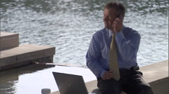 A businessman answers his phone, while working on his laptop. Stock Footage