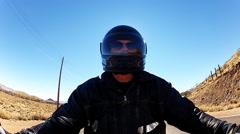 Helmeted Motorcycle Rider On Desert Highway- Backlit Stock Footage